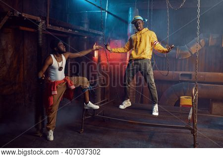 Two rappers posing, performing in cool studio