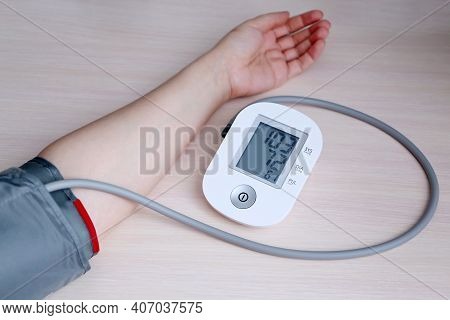 Woman Measuring Blood Pressure With Electronic Digital Tonometer, Female Hand Close Up. Arterial Hyp