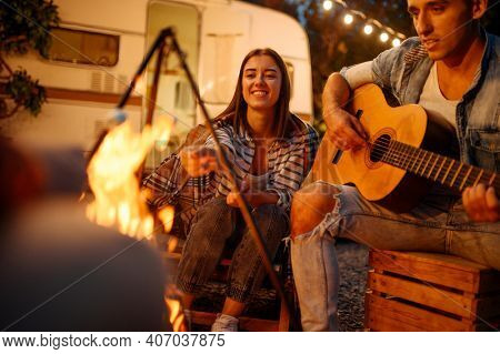 Friends playing on guitar by the bonfire, camping