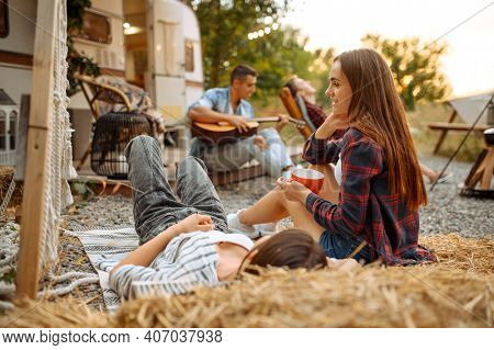 Friends sing songs with guitar, picnic at camping