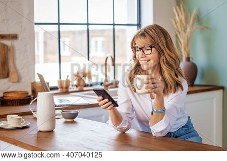 Smiling Mature Woman Drinking Her Coffee In The Kitchen At Home