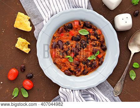 Large Beans Stewed With Tomatoes, Apple And Bell Peppers In A Gray Plate On A Brown Concrete Backgro