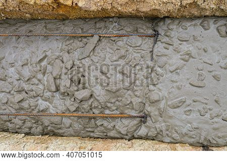 Freshly Poured Reinforced Concrete In A Trench. Construction Of A Monolithic Strip Foundation Of A B