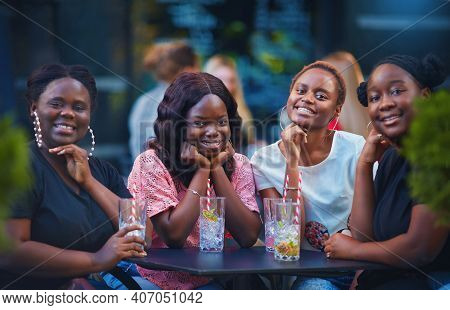 A Group Of Beautiful Happy African American Women, Girls Chilling Out At Summer Outdoor Cafe, Drinki