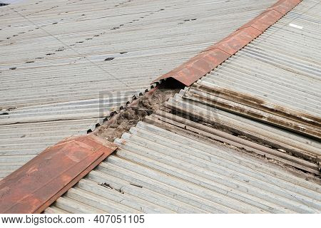 Old Damaged Metal Profiled Sheet Roof. Defective Steel Roof Ridge.