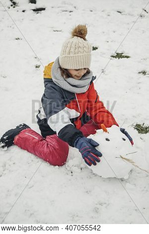 Snow Games, Entertainment And Fun. A Cute Caucasian Girl Sculpts A Snowman In The Yard. Decorates Th