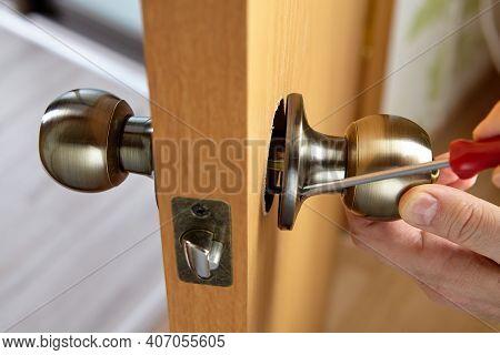 Carpenter Fixes Door Knob With Lock And Latch On New Door.