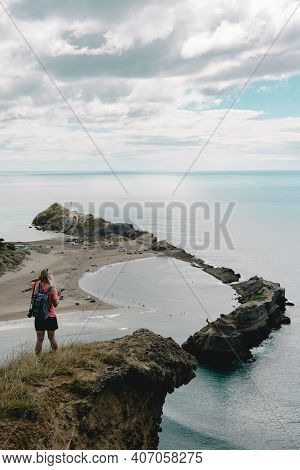 Girl On Castle Rock Lookout Point Seeing Lighthouse At Castle Point. New Zealand Landscape.