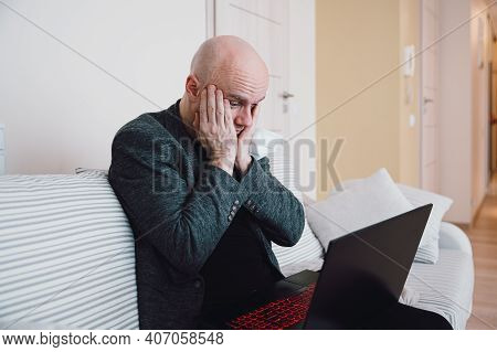 Businessman Looking At Laptop Screen Sitting On The Sofa. He Received Bad News.