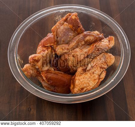 Chicken Buffalo Wings Raw In Bowl With Honey Barbcue Sauce Flavored On An Isolated Background.