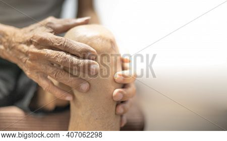Close Up Of Old Man Hand Holding On The Knee With Suffering From Knee Pain. The Sick Legs Of An Old