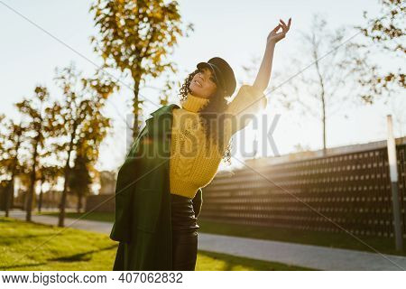 The Free Girl Threw Her Hands Up And Danced. Autumn Park At Sunset. High Quality Photo