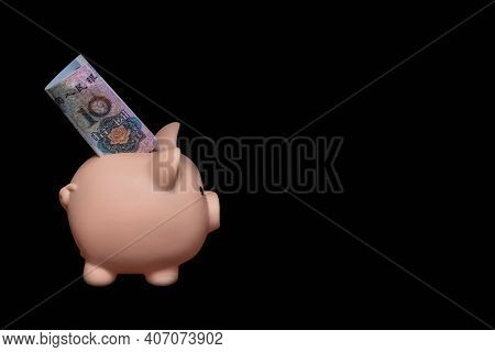 A Piggy Bank With A 10 Yuan Bill Inside On A Black Background. The Concept Of Saving Money. Careful
