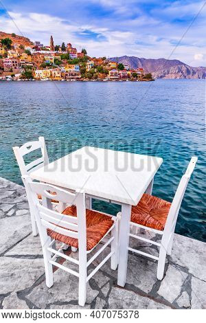 Symi, Dodecanese Islands Of Greece. White Chairs With Tables In Typical Greek Tavern Near The Sea In