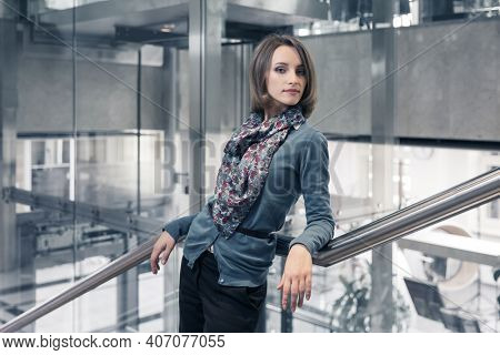 Young fashion business woman leaning on railing in office interior  Stylish female model in blue cardigan and silk scarf