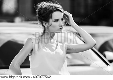 Young business woman on city street Stylish fashion model with bun updo hair style in white sleeveless blouse