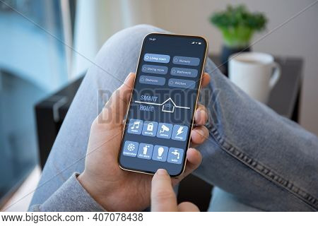 Male Hands Hold Phone With Smart Home Application On The Screen In Room House