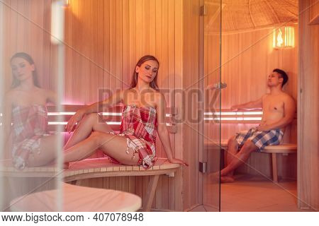 Woman and man in the sauna relaxing in the heat