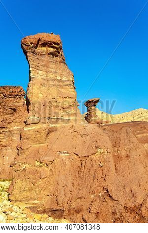Eilat Mountains. Multicolored landscape formations. Israel. Bizarre forms of weathered sandstone in the mountains. Hot November day in the stone desert.