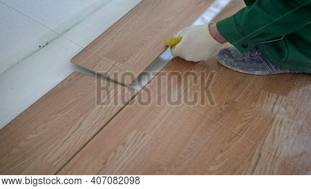 May Laying Laminate Flooring At Home. Installing Laminated Floor, Detail On Wooden Tiles Ready To Be