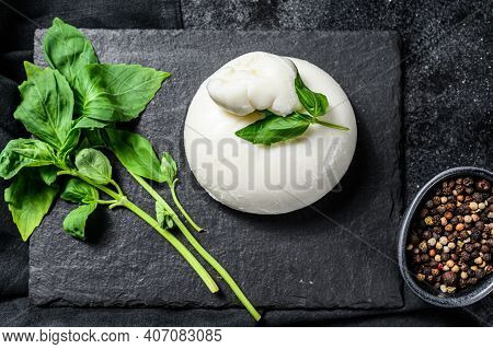 Mozzarella Burrata Cheese With Basil Leaves. Black Background. Top View