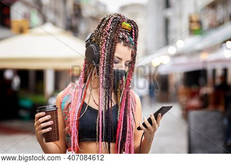Playful Cool Rebel Funky Hipster Young Girl With Face Mask Searching For Playlist Music On Mobile Ph