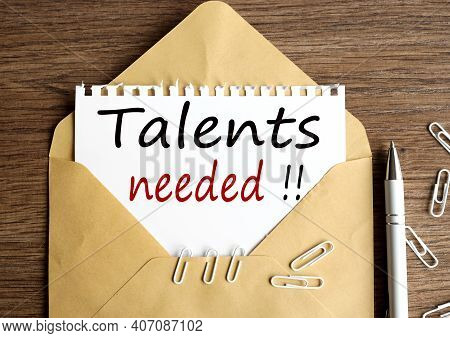 Talents Needed. Text On White Notepad Paper On Craft Envelope On Wood Background.