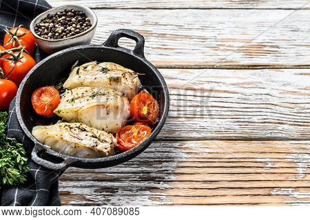 Fried Cod Fish Fillet With In A Cast Iron Pan. White Background. Top View. Copy Space