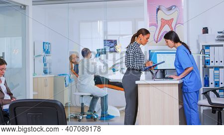 Professional Dentist Asking Nurse For Dental X-ray Before Examining Patient While People Waiting In