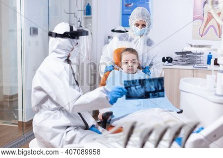 Dentist With Face Shield And Ppe Suit In Dental Clinic Discussing About Caries Using Radiography. St