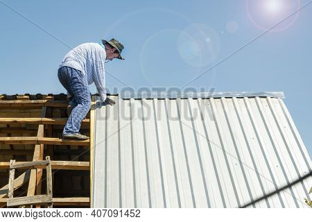 Carpenter Repairs The Roof Of The House, Attaches Metal Galvanized Sheets In Hot Weather In The Brig