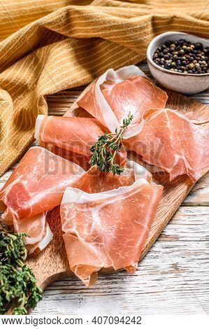 Spanish Jamon Serrano On A Cutting Board, Cured Ham. White Wooden Background. Top View