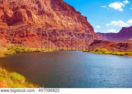 Historic boat crossing Lee's Ferry. Smooth turn of the magnificent Colorado River. USA. Amazing wildlife. Steep river banks of red sandstone. The concept of active, extreme and photo tourism
