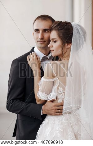 Wedding Couple. Bride With Wedding Bouquet Holds The Grooms Arm. Stylish Newlywed Couple. Marriage C
