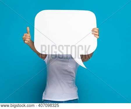 casual woman hiding behind a speech bubble and giving a thumbs up against blue background