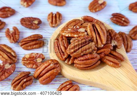 Wooden Spoon Full Of Pecan Nuts With Many Kernels Scattered On Pale Blue Wooden Table