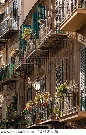 Building exterior with wooden shutters and balconies in Sicily, Italy. Typical sicilian facade of the building.
