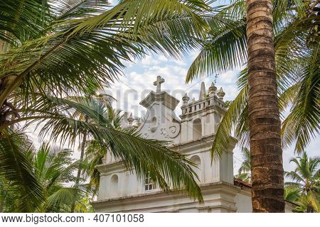 Portuguese christian church among coconut palm trees in Goa state, India