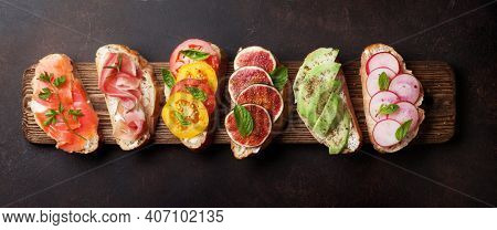 Brushetta or traditional spanish tapas. Appetizers italian antipasti snacks set on wooden board. Top view flat lay