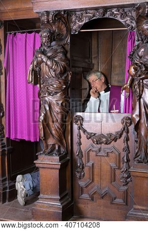Priest listening to the sins of a person in a confession booth