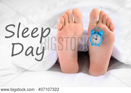 . Sleep Day. A Man Lies In Bed, An Alarm Clock Hangs On His Leg, The Concept Of Laziness, World Slee