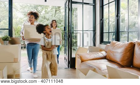 Happy African American Young Family Bought New House. Mom, Dad, And Child Smiling Happy Hold Cardboa