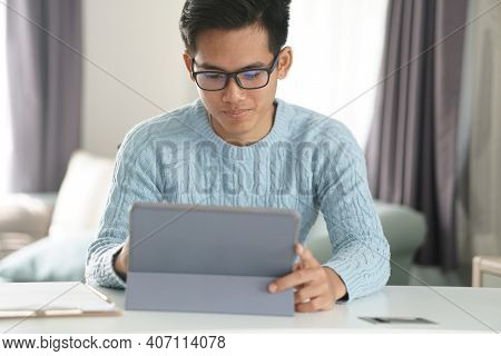 Asian Young Student Man Entrepreneur Working With Tablet Studying Learning Online At Home. E-learnin