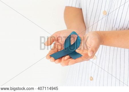 Hand Holding Teal Color Ribbon On White Isolated Background, Copy Space. Ovarian Cancer Awareness, G