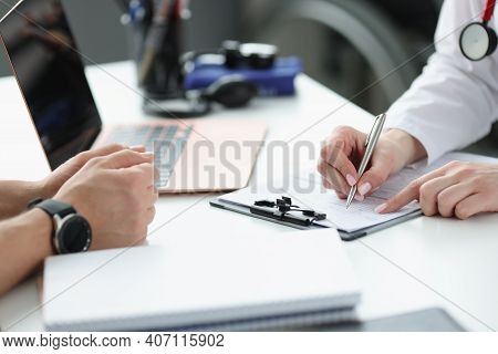Doctors Hands Writing Down Patients Complaints In Medical History Closeup. Medical Consultation Conc