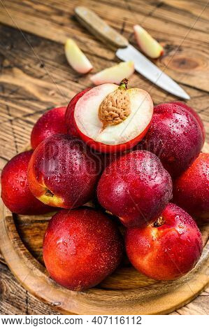 Red Nectarines On A Wooden Tray And Half A Nectarine. Wooden Background. Top View