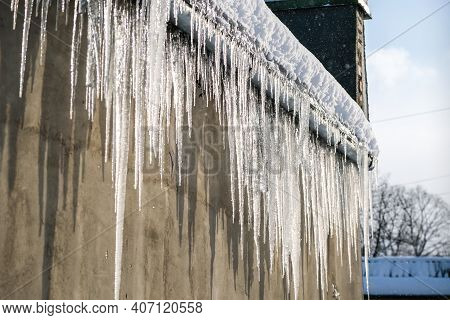 Big, Sharp Icicles And Melted Snow Hanging From Eaves Of Roof. Beautiful Transparent Icicles Slowly