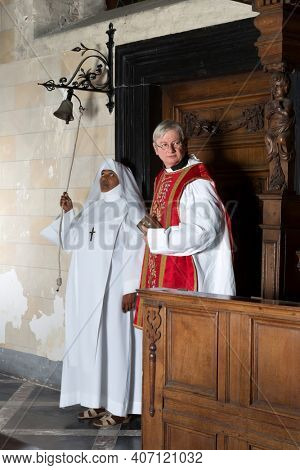 Nun ringing a bell at the beginning of catholic mass in a medieval church