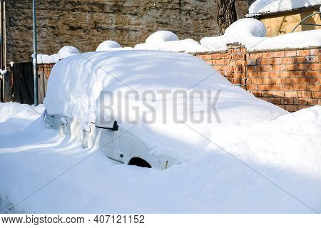 Car Under A Thick Layer Of Snow After Heavy Snowfall
