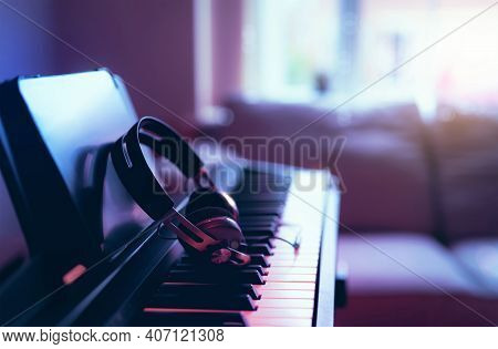 Soft Focus Digital Piano Keyboard With Modern Headphones For Music With Blurry Of Sofa Background, C